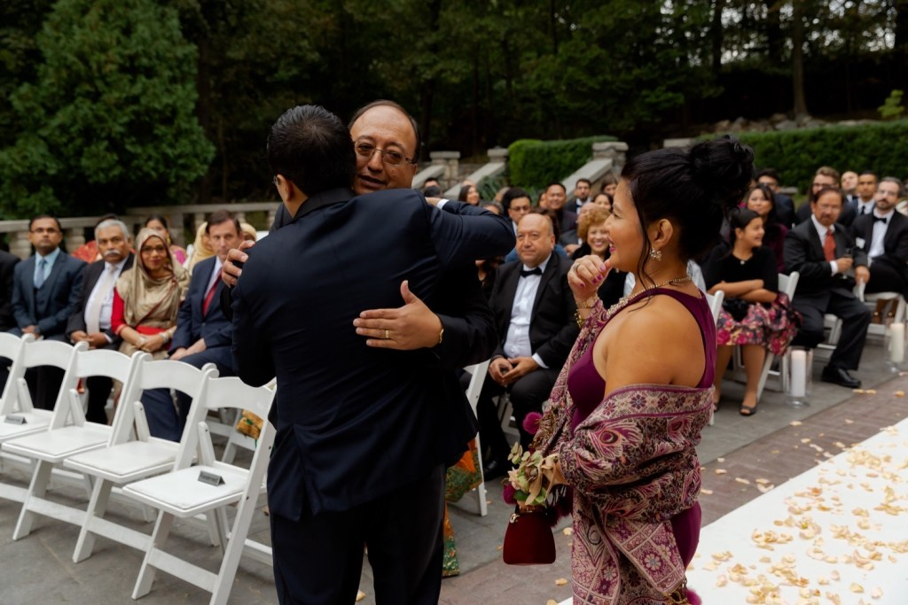 A groom hugging his father during a ceremony at the Tappan Hill Mansion.