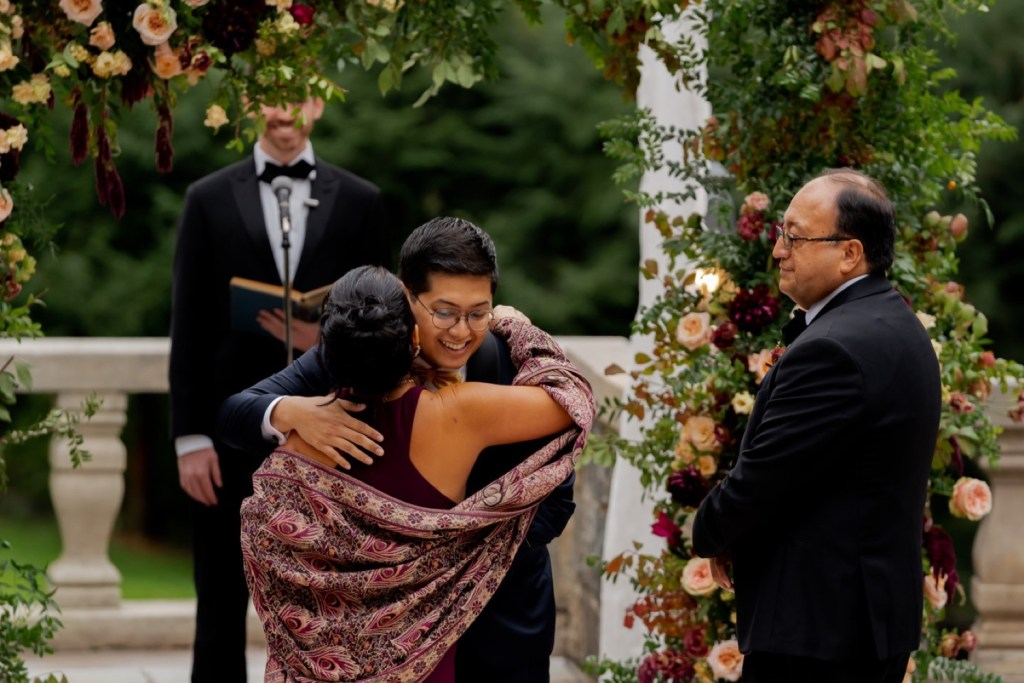 A groom hugging his mother during a wedding ceremony at the Tappan Hill Mansion.