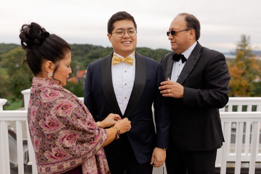 A groom wearing his wedding suit with a help from his family.