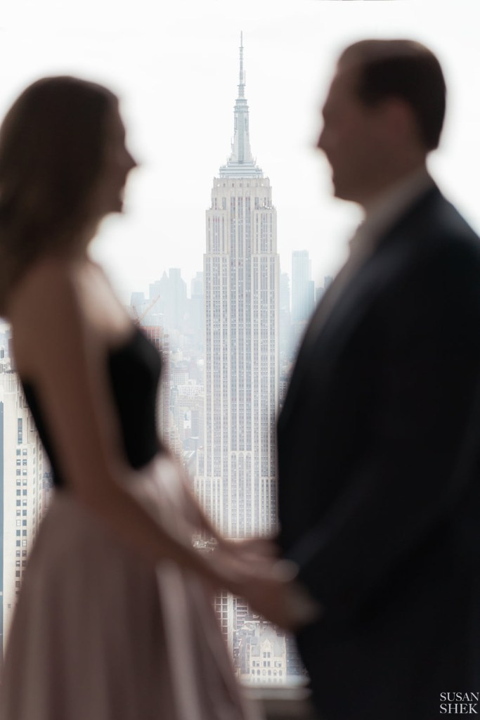 top of the rock indoors with the couple facing empire state building for engagement photos