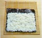 The sushi rice spread on the nori