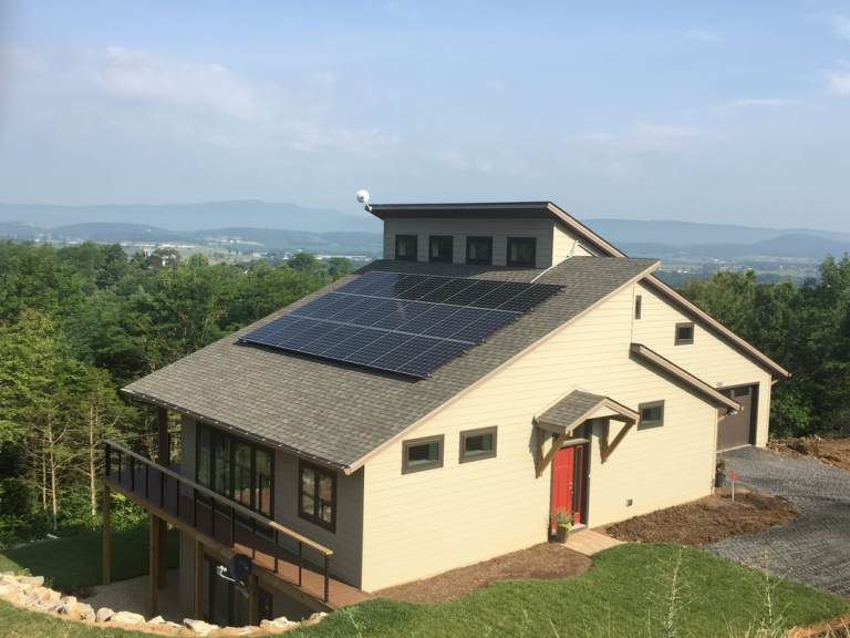 A house outfitted with solar panels and large windows on one side.