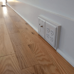 A photo of an electrical wall outlet by the floor, which would be a couple inches away from the wall except that the baseboard reduces the distance to a half inch, and to 0 at the trim.