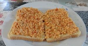 Roerbak ei met ui en tomaat op de boterham