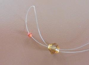 Armband met kralensluiting beide draden door de tweede kraal
