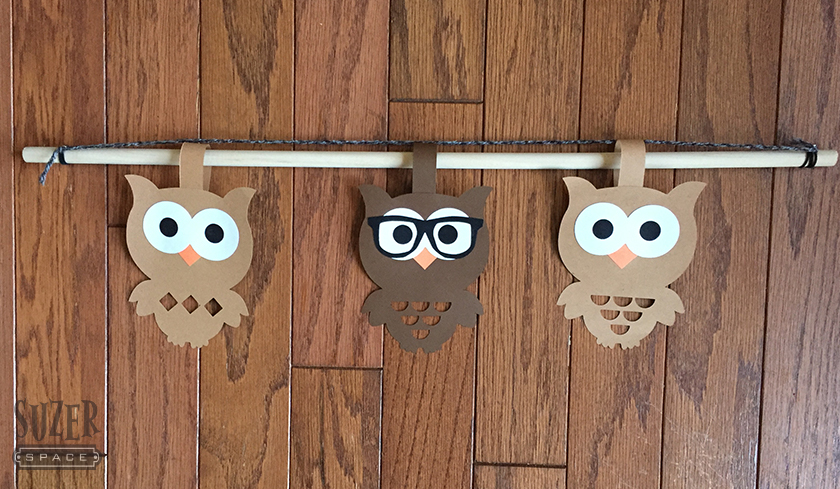 Paper cutout owls assembled on a dowel rod for a door decoration