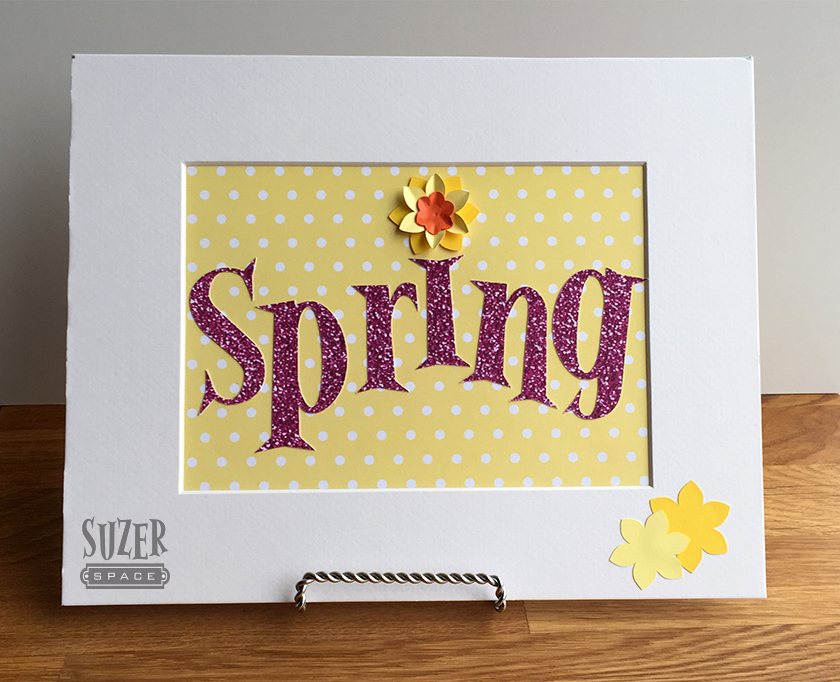 A sparkly spring sign to mark the new season comes together from colorful papers.