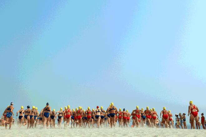 Women lifeguards run along the beach at Gateway National Recreation Area in Sandy Hook, New Jersey, under a wide, clear blue sky.