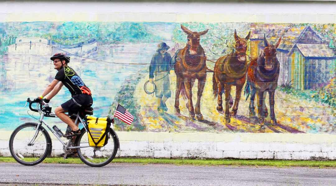 Empire State Trail photos: A colorful cyclist rides past a large painted mural along the Erie Canalway Trail, part of New York's new Empire State Trail.