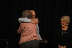 Ann Bizzell gives Ed Wnorowski a hug upon reaching the stage to accept the Lifetime Service Award.