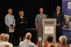 Devon Kroeger accepting the Pay It Forward Award. Back row, from left, Ed Wnorowski, Donna Young and Doug Proffitt.