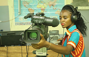 A woman operates a television camera