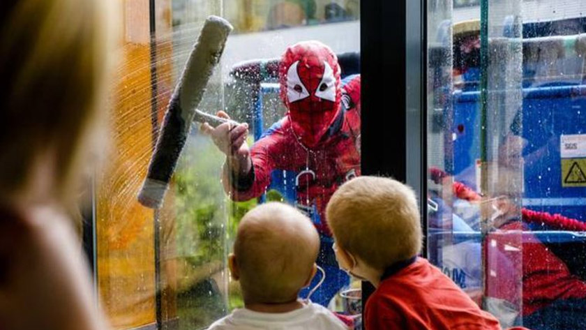 Spiderman wast de ramen van het Koningin Mathilde ziekenhuis.