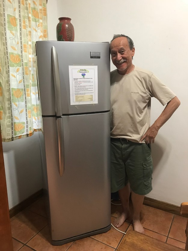 My dad posing by the fridge - which won't fit a pizza box