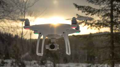 photo of white drone quadcopter flying near trees at noontime