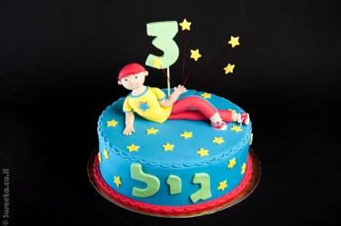 עוגה עם דמות של יובל המבולבל שוכב על עוגה מבצק סוכר