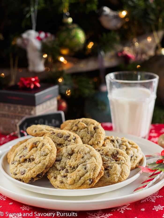 Chewy Chocolate Chip Cookies on white dish with glass of milk