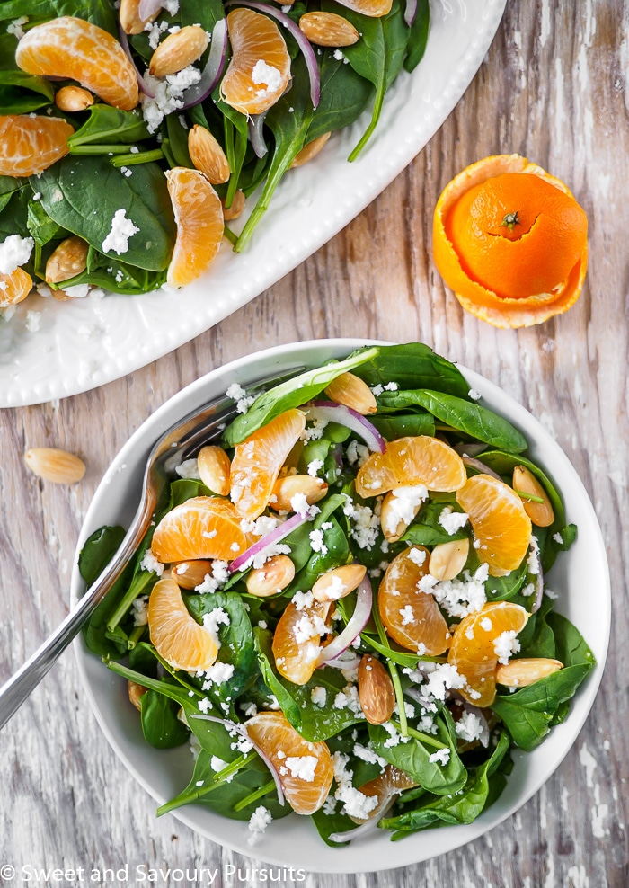 Spinach and Clementine Salad topped with goat cheese and almonds on white dish.
