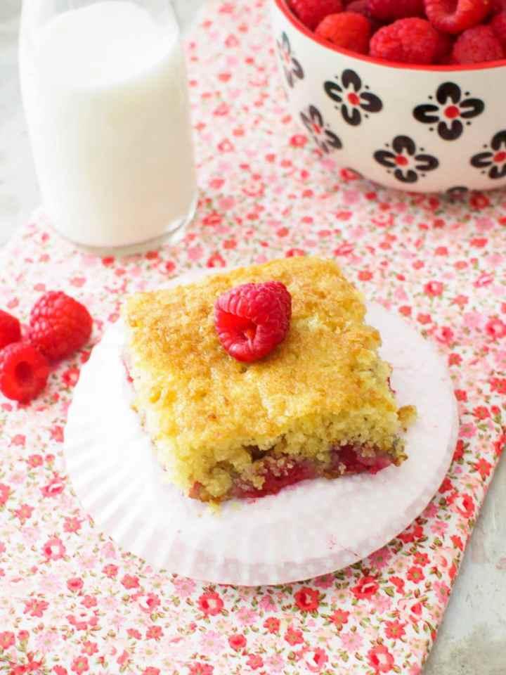 Raspberry Buttermilk Cake served with bowl of fresh raspberries.