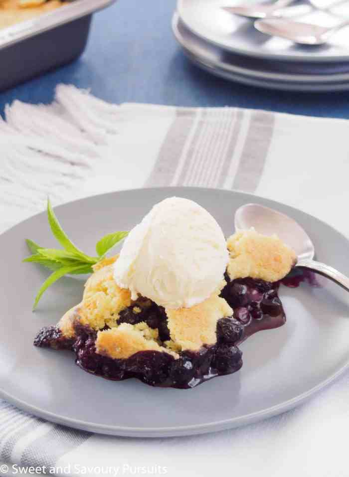 A serving of Blueberry Cobbler with vanilla ice cream on top.