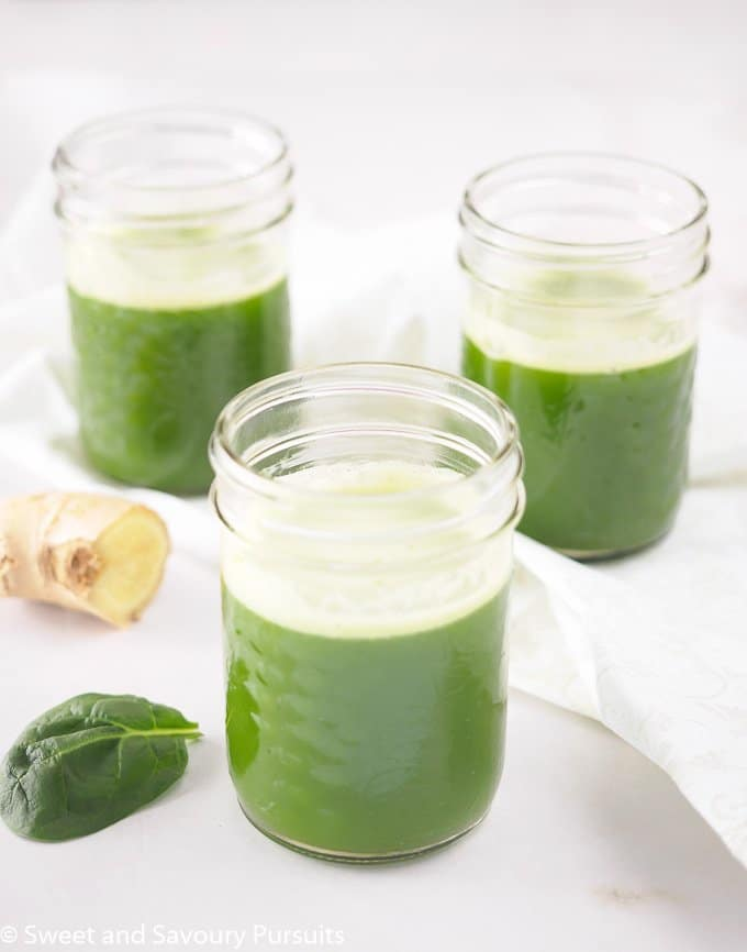 Pineapple Spinach Juice with Ginger served in small mason jars.