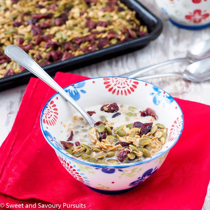 Bowl of nut-free Healthy Pumpkin Seed Granola topped with milk.