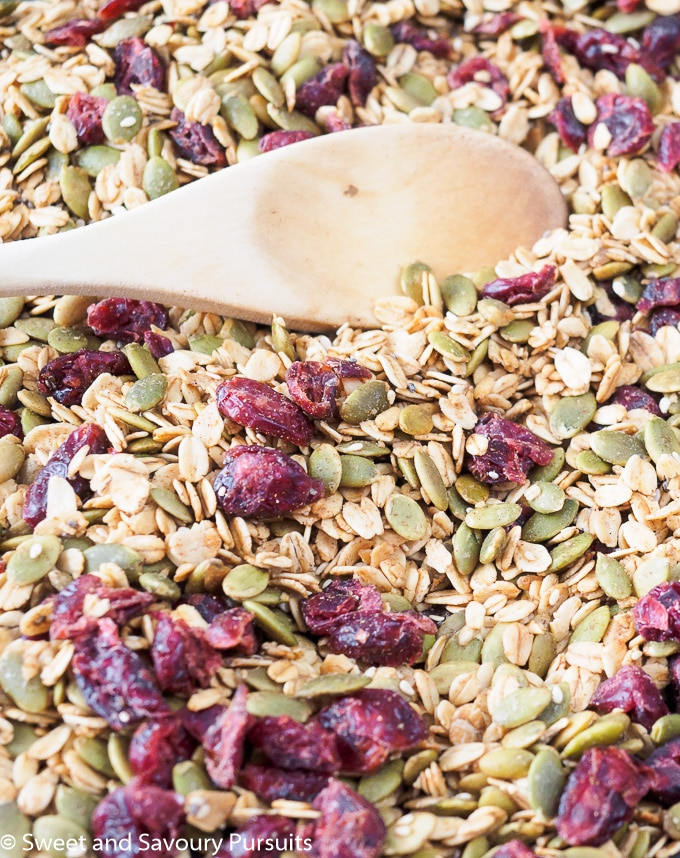 Pumpkin Seed Granola on baking sheet with wooden spoon.
