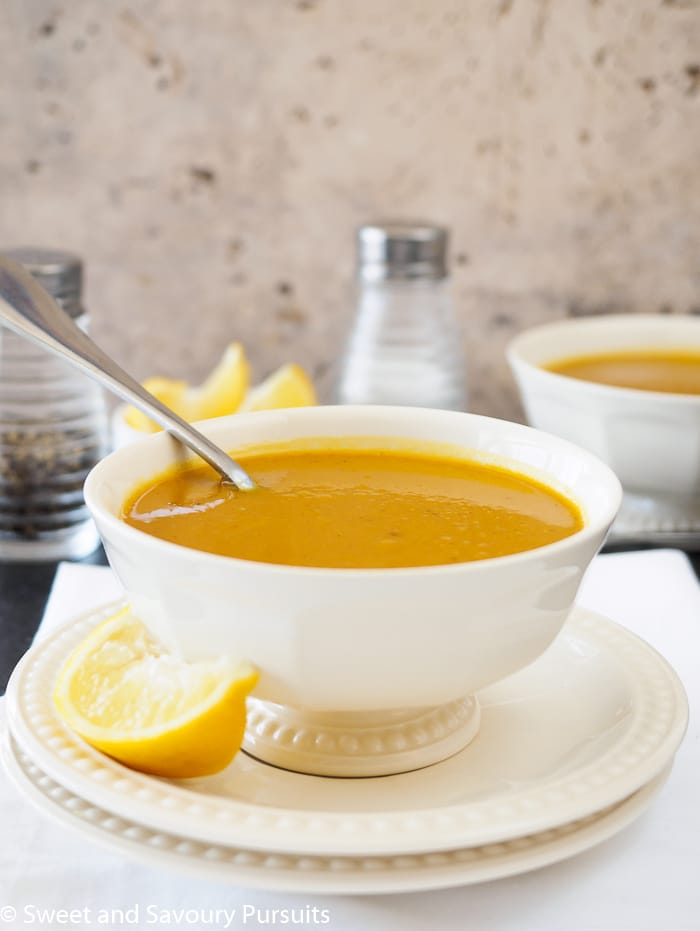 A bowl of Sweet Potato and Red Lentil Soup served with a wedge of lemon.
