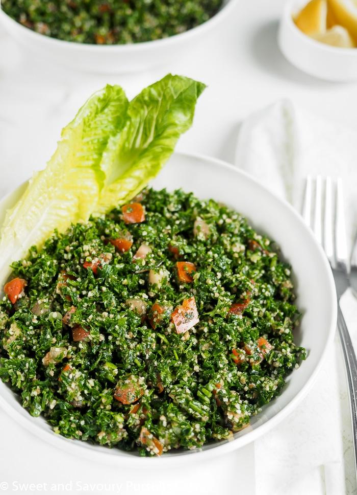 Lebanese Tabbouleh Salad served in bowl with romain lettuce leaves.