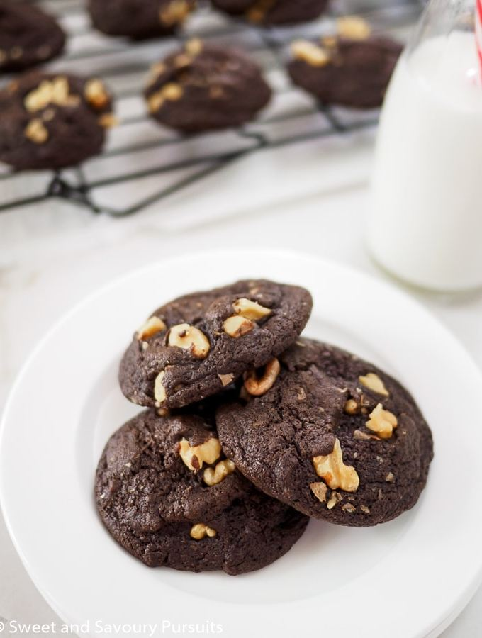 Fudgy Chocolate Walnut Cookies on dish with glass of milk