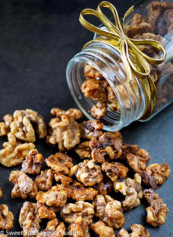 Maple Spiced Walnuts poured out of mason jar onto dark surface.