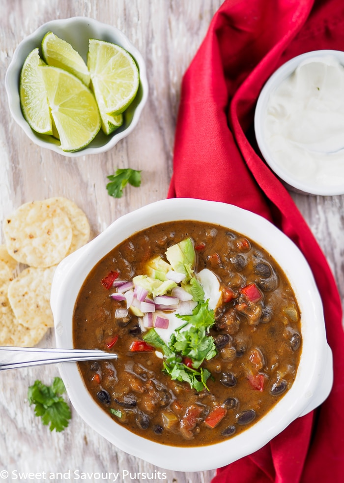 Bowl of Easy Black Bean Soup served with tortilla chips and sour cream.