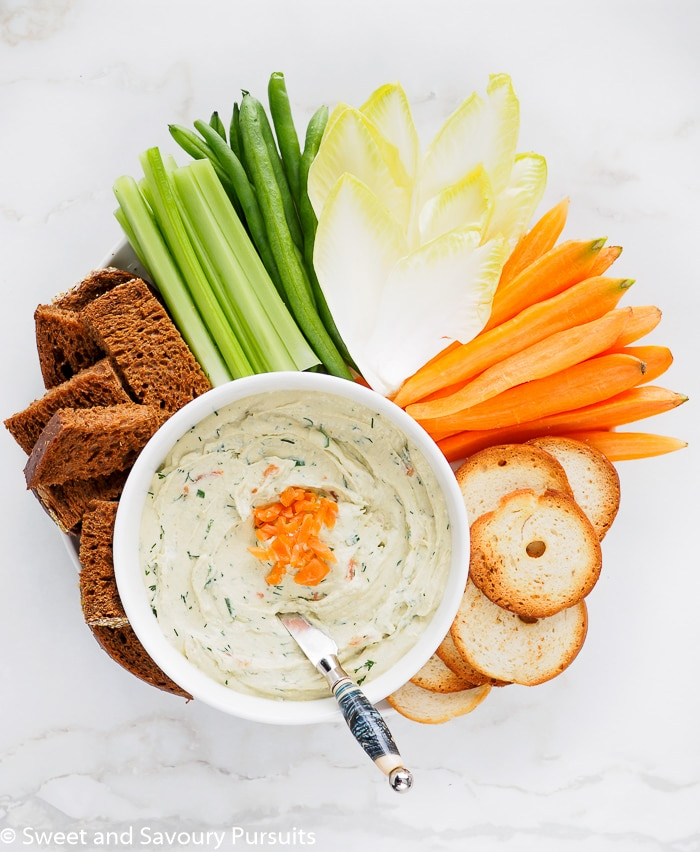 Bowl of Smoked Salmon Cream Cheese Dip with veggies and crackers.