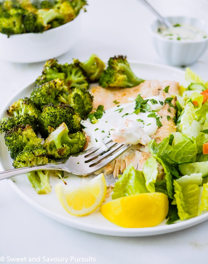 Baked Rainbow Trout Fillets with Roasted Broccoli and salad on dish.