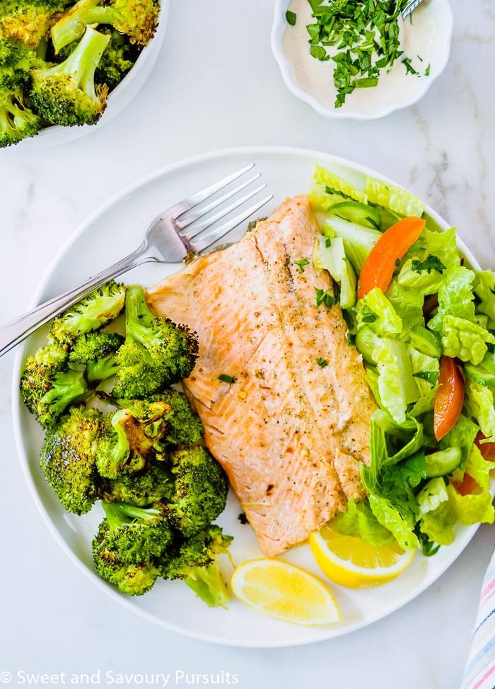 Baked Rainbow Trout Fillets with Roasted Broccoli and salad on dinner plate.