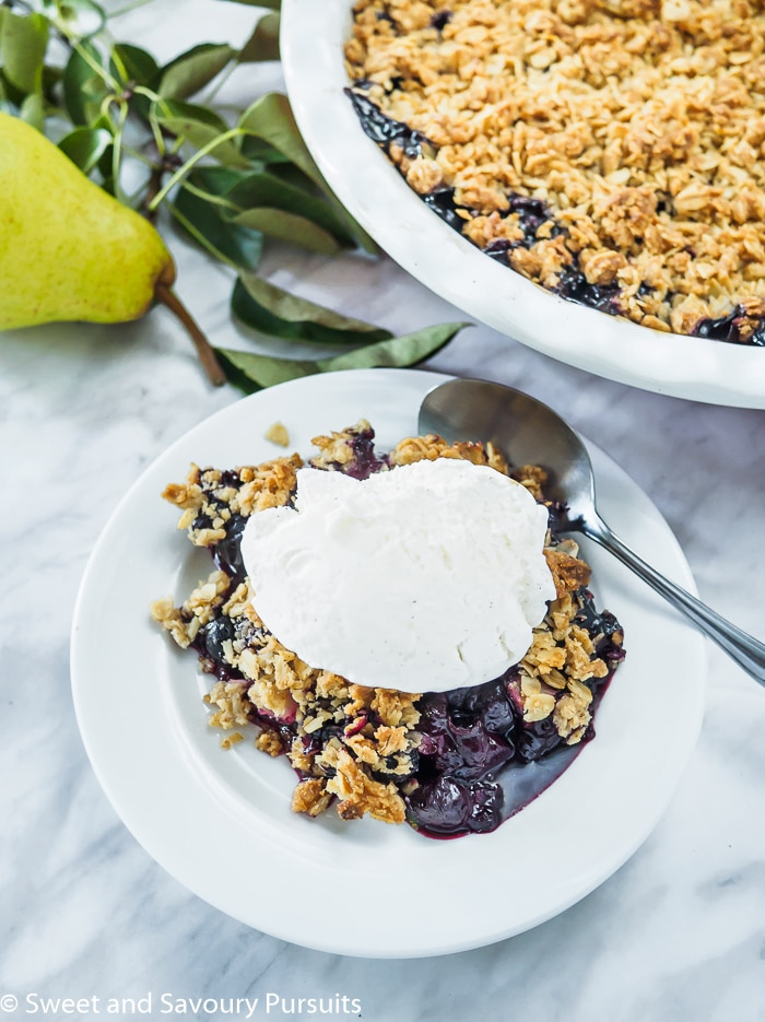 Plate of Pear and Blueberry Crumble topped with vanilla ice cream