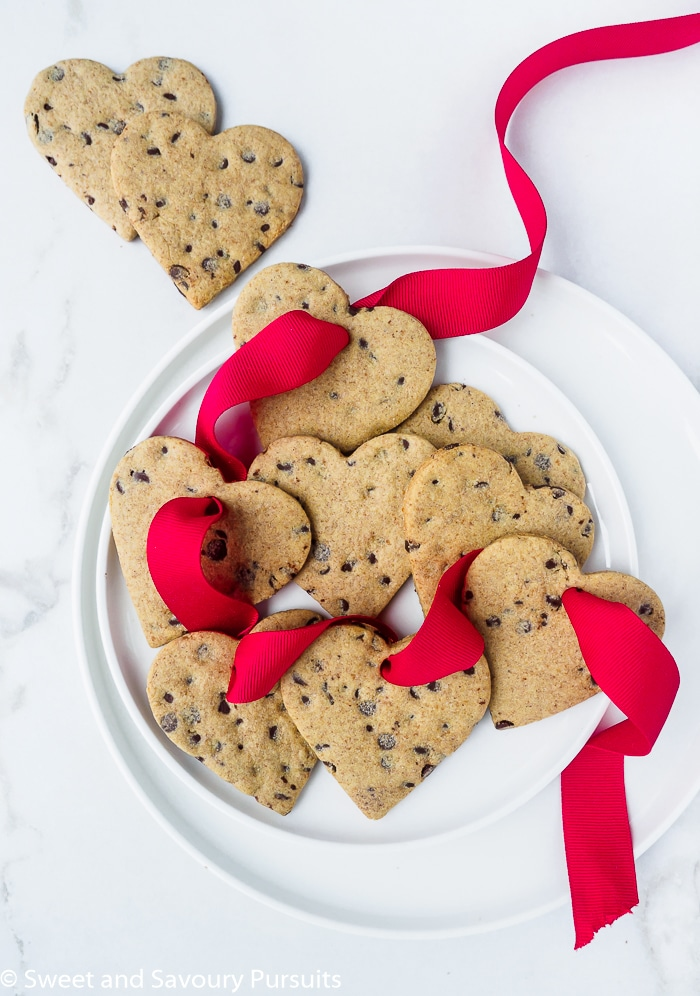 Healthier heart shaped chocolate chip sugar cookies on white dish with red ribbon.