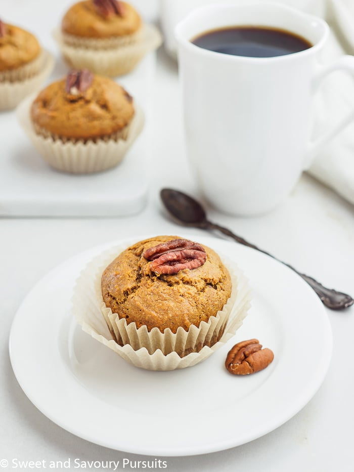 Sweet Potato Muffin topped with a pecan on small dish.