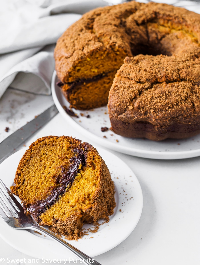 A pumpkin bundt cake with a melted chocolate swirl in the middle and topped with a crumbly brown sugar and spice mixture.