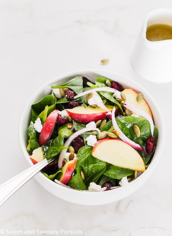 Bowl of Spinach Apple Cranberry Salad with Pumpkin Seeds