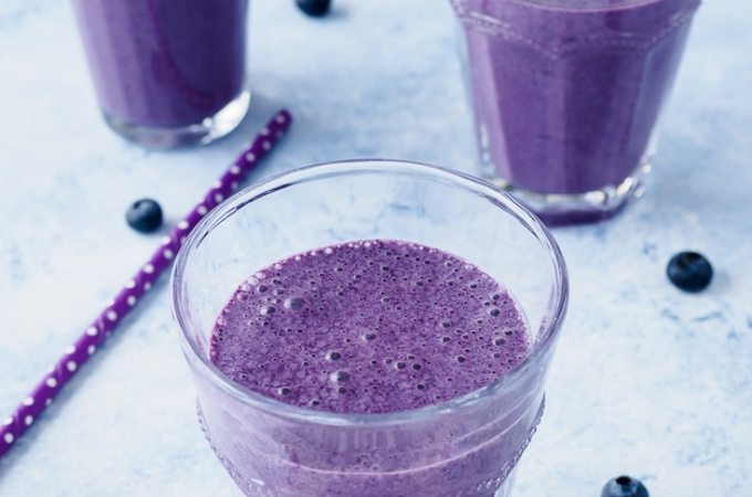 Blueberry Oatmeal Smoothie flavoured with coconut, cinnamon and nutmeg served in glasses.