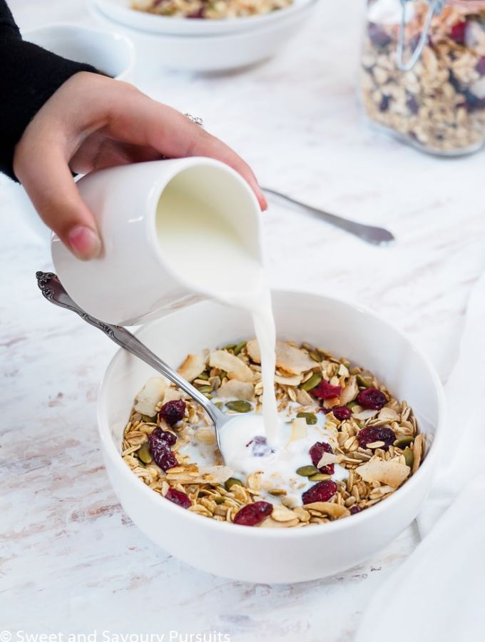 Bowl of homemade muesli made with oats, coconut flakes, pumpkin seeds, sunflower seeds and dried cranberries with milk.