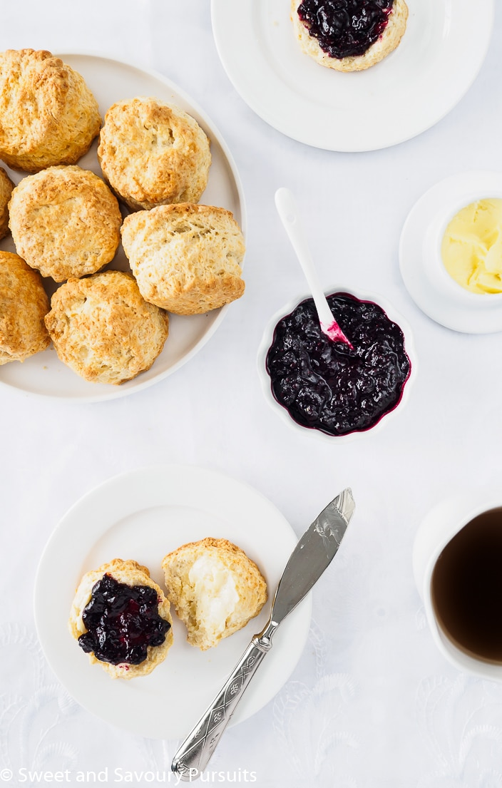 Plate of Irish Scones served with butter, mixed berry jam nd a cup of tea..