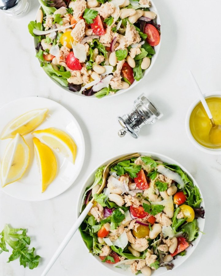 Two bowls of White Bean and Tuna Salad with lemon and olive oil dressing served on the side.
