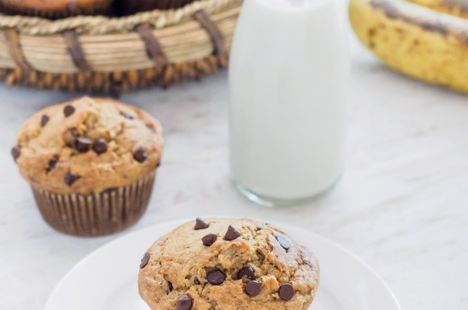 A basket of Banana Oatmeal Chocolate Chip Muffins and one muffin on small dish served with milk.