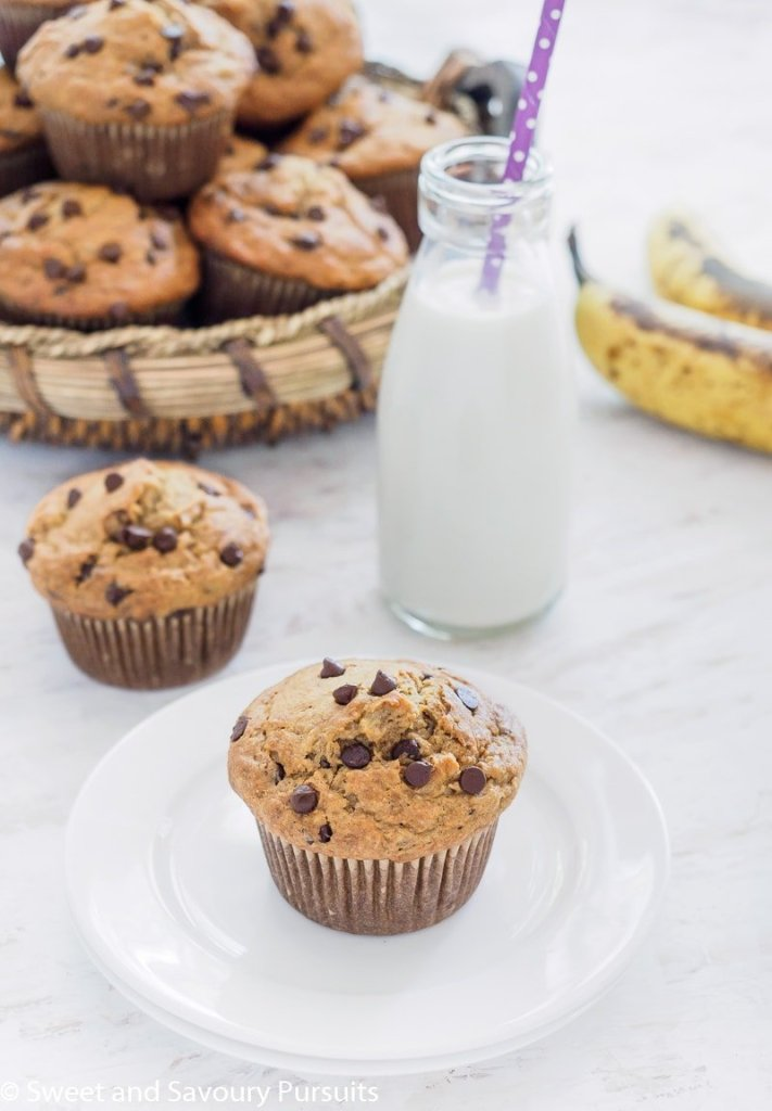A basket of Banana Oatmeal Chocolate Chip Muffins with one muffin on small dish served with milk.