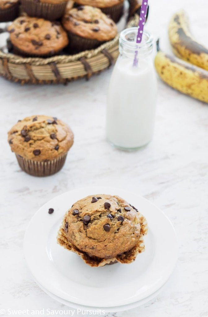 Banana Oatmeal Chocolate Chip Muffin on small white dish served with milk in small bottle.