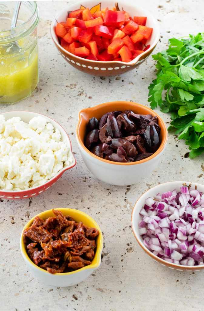 Picture of ingredients needed for a Mediterranean Pasta Salad. There are small bowls of Kalamata olives, red onions, Feta cheese, sun-dried tomatoes and parsley.