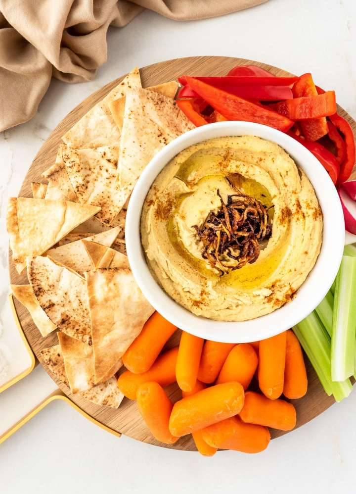 Plate of hummus with pita chips and fresh vegetables.