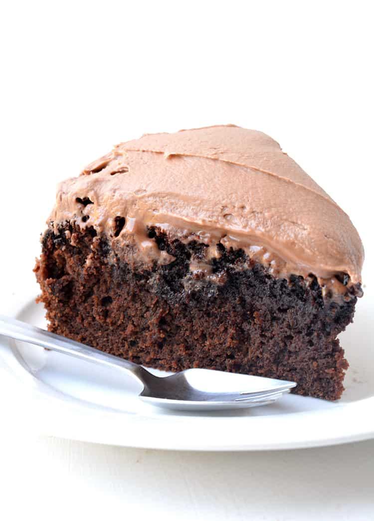 A slice chocolate mud cake on a white plate